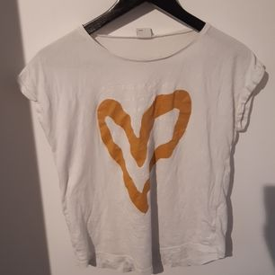 En vit t-shirt med guldigt hjärta och text. Några år gammal. Använd få gånger. Bra skick. Liten i storleken
