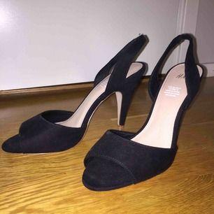 Högklackade skor med mocka tyg och klack 11cm. Skorna är rätt slitna under men det är inräknat i priset. Borde inte göra så mycket då den sidan ändå är mot marken.
