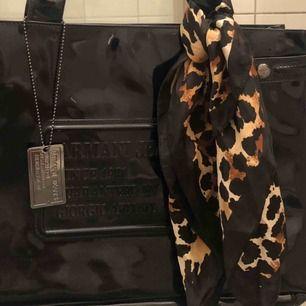 Handväska från Armani Jeans har en svart lackad yttre präglad med Armani jeans logotyp och en matchande metallbricka. En magnetlås visar en textil inre med flera fack och en dragkedja I fint begagnat skick Nypris 1200:- Mitt pris 600:-
