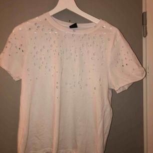 """En vit T-shirt med """"hål"""" i från gina tricot! Superfin på, hålen är inte över bysten så man """"ser inget"""" utan ser mer ut som prickar på T-shirten!! Har tyvärr inte kommit till användning för mig dock, mer än 1-2 gånger. ⚡️"""