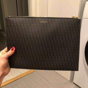 Säljer min Saint Laurent pouch!  Köpt i München för något år sen Skick: varsamt använd, som ny unisex Den är gjord av canvas, ej läder
