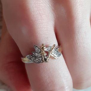 En ring i både guld och silverfärg, med en jättesöt älva på som liknar tingeling💛Frakt: 11:-