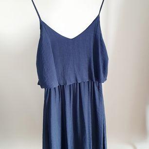 Midiklänning i siden med fint flow. Passar sommarfesten, bröllop eller till vardags.