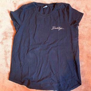 """15kr + frakt tillkommer. Kan mötas upp i Linköping 💖 Marinblå t-shirt med text """"Brooklyn"""" på vänster bröst. Knappt använd!"""