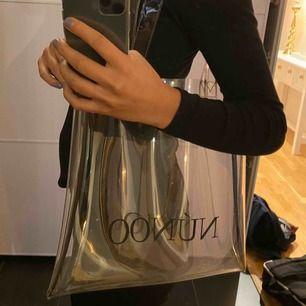 Genomskinlig väska från Nunoo. Väldigt fin!! Original pris: 349kr. Mitt pris 159kr Köparen står för frakten
