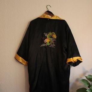 Sjukt fin vändbar vändbar kimono, storlek L. Men passar även större och mindre storlekar. Ena sidan är svart med en drake på ryggen. Och andra är gul med blommor och svarta detaljer. Frakt 44 kr