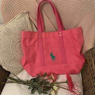 Denna väska är en Original Ralph Lauren Tote Bag i färgen rosa. Perfekt som en lyxig skolväska, strandväska eller shoppingbag då den är rymlig men ändå inte så jätte stor! Original pris ligger på 995 kronor. Denna är endast använd en gång.