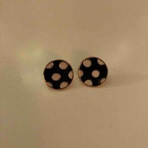 Runda svarta örhängen med vita prickar och guldiga kanter. Aldrig använda