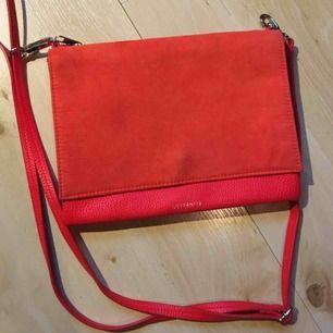 Säljer en superfin röd väska från Hm som man kan använda som en axelremsväska eller kuvertväska💋Den är i fake skinn/mocka & är bara använd en kväll❣️