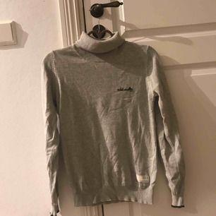 En ljusgrå polo tröja, med ett skönt och tunt material. Helt oanvänd