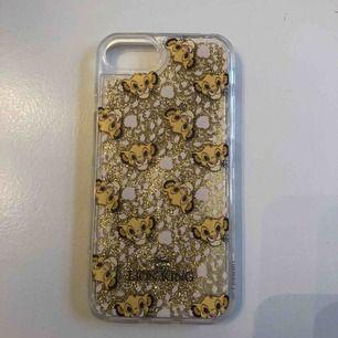 """Ett mobilskal med lejonkungen med gulligt glitter som """"flyter"""" runt. Passar iPhone 6/7/8. Aldrig använt, endast testad. Pris ink frakt."""