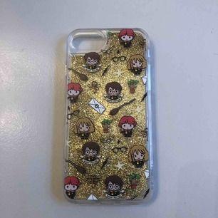 """Mobilskal med Harry Potter-tryck och guldigt glitter som """"flyter"""" runt. Passar iPhone 6/7/8. Aldrig använt, endast testad. Pris ink frakt!"""
