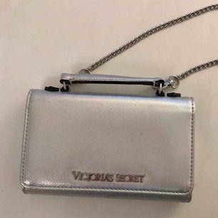 Korthållare som också har en ficka för mobilen, kommer även med en kedja som går att ta av.  Längd: ca. 15.5cm Bredd: ca. 3cm Höjd: ca. 10cm  Använd: två gånger