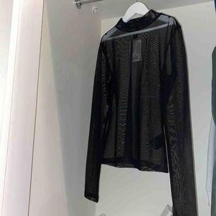 En svart, genomskinlig blus. Har aldrig används, prislappen är till o med kvar.