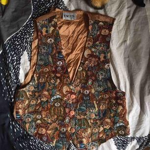 Underbar väst med nallebjörnar i fram och silkestyg på ryggen. Det går att knyta i bak för att justera passformen. Jättefint skick och en snygg detalj till en outfit! Vid frakt står köparen för kostnaden 💌