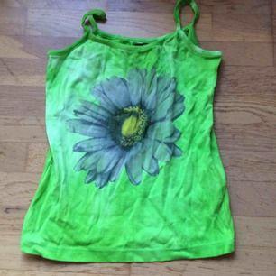 Neongrönt batiklinne med en blomma framtill. Märkt M men litet i storlek så mer en XS-S. Frakt: 42 kr i postens påse