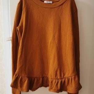 Långärmad tröja med volanger. Rostbrun i färgen
