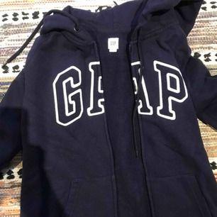 Storlek S. GAP hoodie med dragkedja. Marinblå färg, använd kanske 4 ggr. Väldigt bra skick. Köparen står för frakt