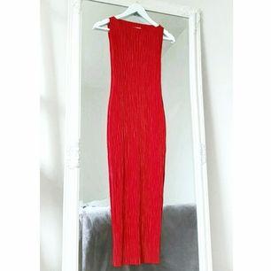 Färg: röd Strl: 34 Längd: 113 cm (från Axel till nedre kant)  Snygg klänning i plisserat stretchmaterial från H&M. Ser exklusiv ut. Skitsnyggt med skärp i midjan också! Hög hals. Liten slits nedtill i kanten. Använd vid ett tillfälle, bra skick