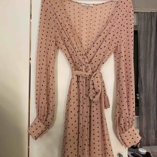 Säljer denna fina klänning, passar perfekt till vår och sommaren. Den är i ljusrosa med svarta prickar och ett band vid midjan. Storlek S. Använd ett fåtal gånger, som ny i skicket! Nypris: 599kr. (Tillkommer frakt)