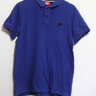 Fin blå pikétröja från Nike. Herr S. Jag på bilden har M och är 167cm. Frakt 44kr
