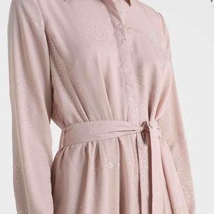 Super fin vadlång skjortklänning i färgen nude (åt det rosa hållet) med guldiga små skimriga prickar. Klänningen heter SFSHADOW LONG DRESS, nypris 999kr. Använd totalt 3 gånger, inga fläckar eller skador, så gott som ny.