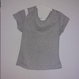 Grå tröja med öppningar vid axlarna, tröjan är även tajt. Köpt i New Yorker