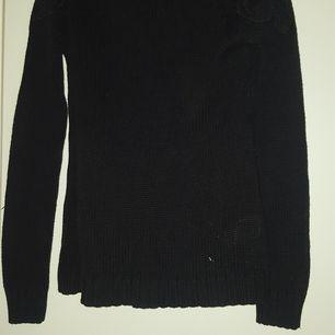 En svart stickad tröja från Gina Tricot den har spets på axlarna. Inte använd så mycket.