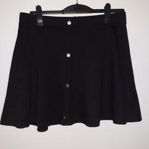 En simpel svart kjol med metallgråa knappar och hänger.
