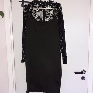 Simpel Svart klänning med blommigspets, tightfitting och har en krage som en choker. Har även en dragkedja på ryggen men klänningen är ganska stretchig.
