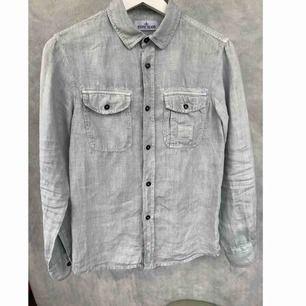 Jag säljer en begagnad Stone Island skjorta, i bra skick. Storlek: 12 år / längd 152. Material: linne / bomull. Färg: ljusgrå. Nypris: ca. 1300 sek.