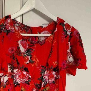 Röd blommig playsuit som man knyter över bröstet som detalj, använd fåtal gånger. Inköpt från barnavdelningen stl 158-164 men motsvarar XS i vuxenstorlek.☺️ (frakt tillkommer)