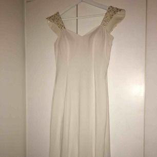 En helt oanvänd vit fest klänning med fina detaljer på baksidan med pärlor och en roset. Den är lång och har ett litet släpp i baksidan. Den är i perfelt skikt. Etiketten finns kvar. Skriv privat för fler bilder. Passar M och L. Pris kan diskuteras