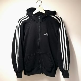 Svart vintage Adidas hoodie i bomull, tyvärr är storlekslappen borttvättad så går inte att se. Snygg detalj är att ränderna går bak på luvan också när man har den uppe, skickar gärna bild. Sitter oversize på mig som har stl XS och känns som att den är en