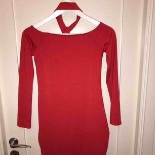 """Kort, tajt och röd klänning från Bikbok. Klänningen har en fast """"spänne"""" eller """"choker"""" runt halsen. Inte använd alls. Kontakta mig om ni är intresserade för mer information!"""