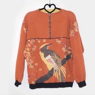 En secondhand pärla. Unik orange kofta med blommor och fågel som motiv. Skick: secondhand, defekt fri.