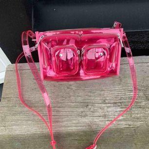 BUDGIVNINGEN SLUTAR SÖNDAG💞Snygg väska från  nunoo i rosa plastmaterial som inte finns på att köpa på nunoo längre.   Nypris: 1000kr  Mått: 15x25 cm.   Bandet går att förkorta och förlänga. Använd en gång. LÅGG BUD!