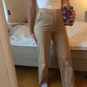 Ett par riktigt bekväma byxor av bra kvalité! En beige färg med fickor både bak och fram. Stretchiga och skönt material. Högmidjade och utsvängda ben. Jag är 1.70 och brukar bära storlek 36. Frakt tillkommer och betalning sker via swish. ☺️