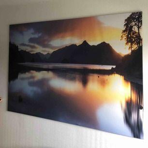 Stor tavla på en sjö med berg och solnedgång i bakgrunden. Den väger väldigt lite så den är lätt att transportera och sätta upp. Fint skick. Mått Höjd: 55cm Bredd: 80cm
