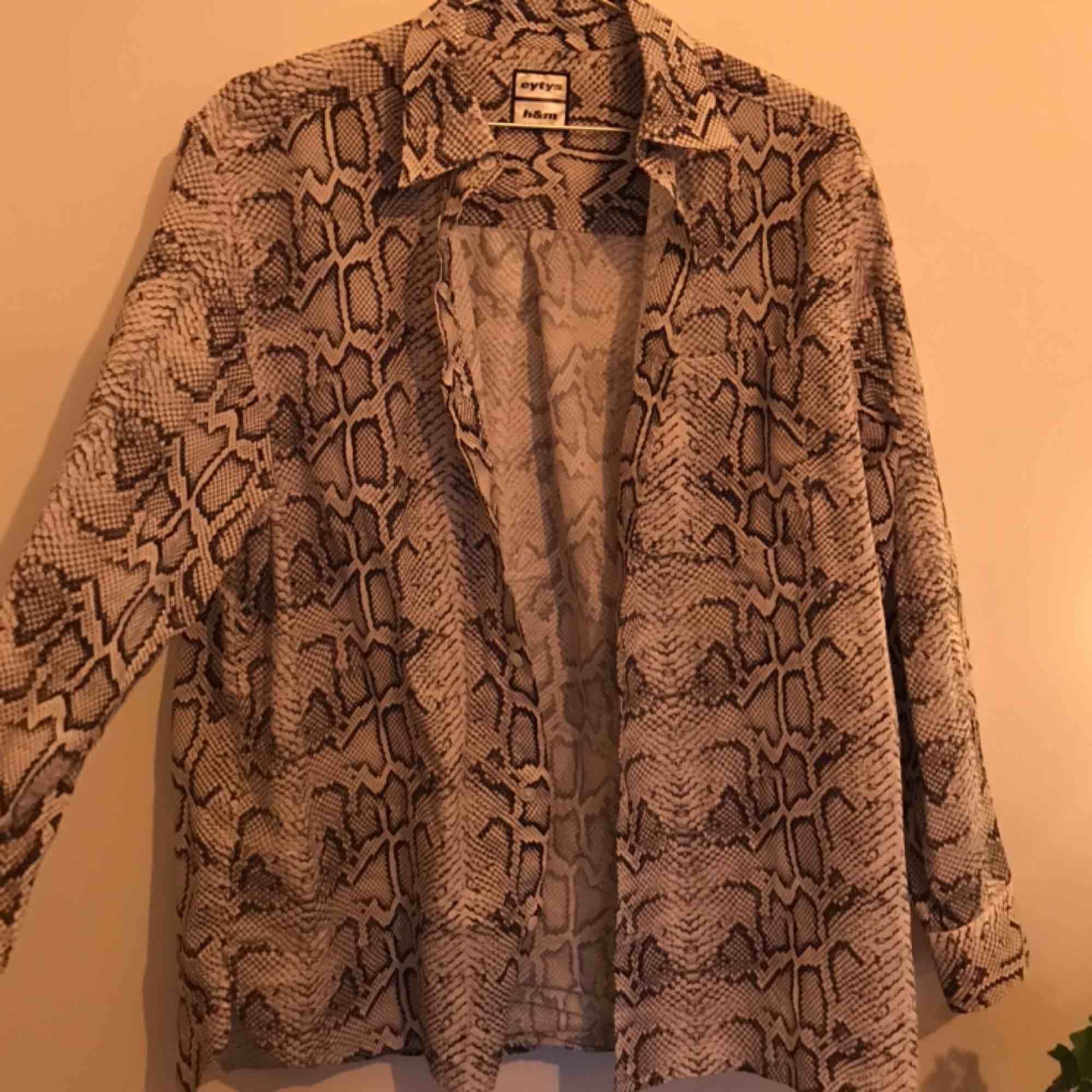 Ormmönstrad skjorta från Eytys kollektion med H&M. Använd max 3 gånger och i väldigt bra skick. Den är ganska oversized så kan passa olika storlekar. Skriv för mer bilder/info. Kan mötas upp i Gbg/köparen står för frakt❤️. Skjortor.