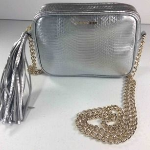 Silvrig mini väska ifrån Victoria secret. Mycket bra skick och knappt använd. Frakt tillkommer❤️