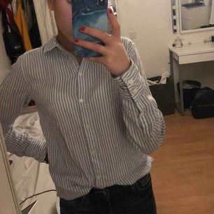 En jättefin skjorta som är blå vit randig från H&M. Använd 1 gång, Frakt tillkommer