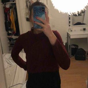 En vinröd tröja med polo i halsen. Längst ner på tröjan är den svart. Frakt tillkommer
