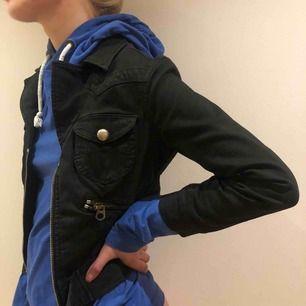 En svart jeans-jacka med mycket detaljer. En kort modell som snygg och enkel att matcha med det mesta!