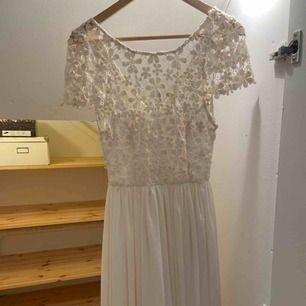 Vit sommar/studentklänning. Finns en liten reva vid klänningens vänstra ärm men går att åtgärda enkelt!