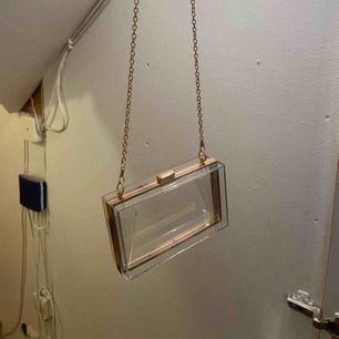Snygg handväska i hårdplast med guldiga detaljer!