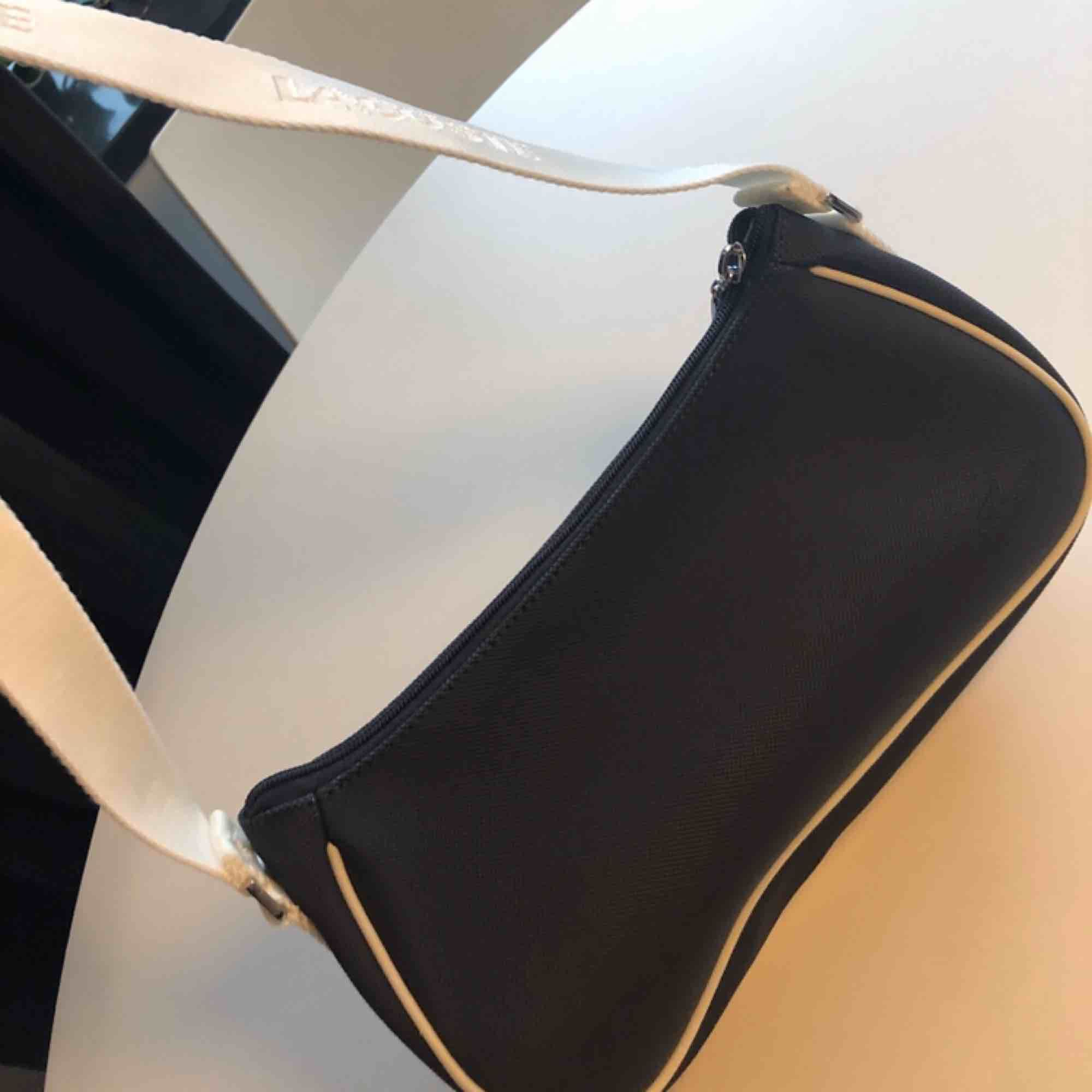 Axelremsväska Lacoste nyskick förutom liten fläck på insida kan skicka bild i övrigt väldigt fin köpt för ca 1500:-. Accessoarer.