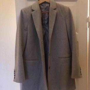 Säljer en grå kappa från Henri Iloyd. Kappan är aldrig använd och därför i ett bra skick.