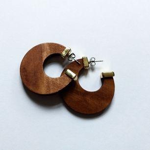 Örhängen i trä med guldiga detaljer. 3.5 cm i diameter. Frakt på 11 kr tillkommer.