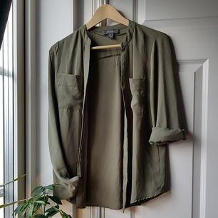Superfin och skön skjorta i mörkgrönt/millitärgrönt tyg!😍 Storlek 34 men funkar även för 36 skulle jag tro. Är i jättebra skick förutom att det saknas en knapp på ena ärmen, lätt att vika upp så funkar det! Köparen står för frakten!